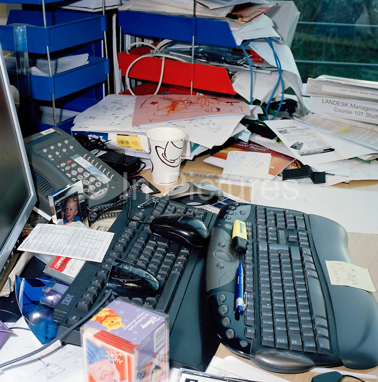 Clutter and office debris at the desk of an employee, Leeds, UK.  From the series Desk Job, a project which explores globalisation through office life around the World.