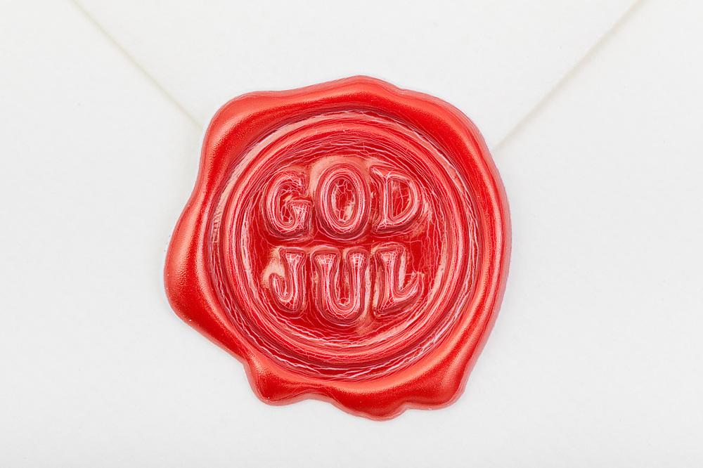 Nærbilde av rødt vokssegl med teksten «god jul», som forsegler en hvit konvolutt.
