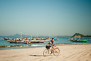 Myanmar, Ngapali. Boys ride a bicycle at the beach.<br /> Every single morning all the fisherman from the little village at Ngapali Beach come back home with their night catch. At the beach all the women wait for them and afterwards work with drying and selling fish and other creatures from the sea begins.
