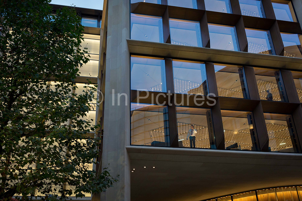 An employee with Bloomberg works beneath bold, modern architecture by Fosters + Partners in the companys new Europeann headquarters on Cannon Street in the Square Mile, the heart of the capitals financial district, on 2nd October 2017, in the City of London, England.