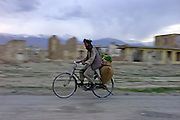 An Afghan cycles along a street devastated by decades of war in an area of Kabul close to the old museum.