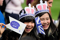 ©  London News Pictures. 21/04/2016. Windsor, UK. Tourists wearing papers crown gather ahead of a walkabout by Queen Elizabeth II through the town of Windsor, Berkshire on the day of her 90th birthday.  Photo credit: Ben Cawthra/LNP