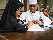 16 JULY 2013 - BANGKOK, THAILAND:  Students in a Koranic studies class at Jami Ul Khoy Riyah Mosque in the Ban Krua section of Bangkok. Ban Krua is the oldest Muslim section of Bangkok. It was established during the reign of Rama I, the first King of the Chakri dynasty. He enlisted Cham Muslims in what is now Cambodia to fight on the Siamese (Thai) side of war between the Khmers and Siamese. He rewarded their service with a grant of land that is now Ban Krua.         PHOTO BY JACK KURTZ