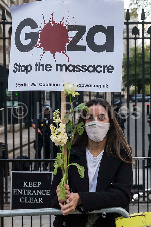 A woman holds a Stop The War Coalition placard outside Downing Street as thousands of people attend an emergency rally in solidarity with the Palestinian people organised by Palestine Solidarity Campaign, Friends of Al Aqsa, Stop The War Coalition and Palestinian Forum in Britain on 11th May 2021 in London, United Kingdom. The rally took place in protest against Israeli air raids on Gaza, the deployment of Israeli forces against worshippers at the Al-Aqsa mosque during Ramadan and attempts to forcibly displace Palestinian families from the Sheikh Jarrah neighbourhood of East Jerusalem.
