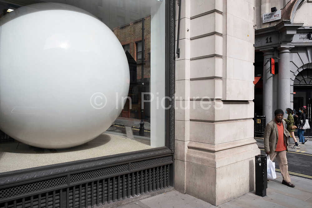 Large white sphere ball in the window of a building on 1st July 2020 in London, United Kingdom. This huge scale sphere interacts with passing people.