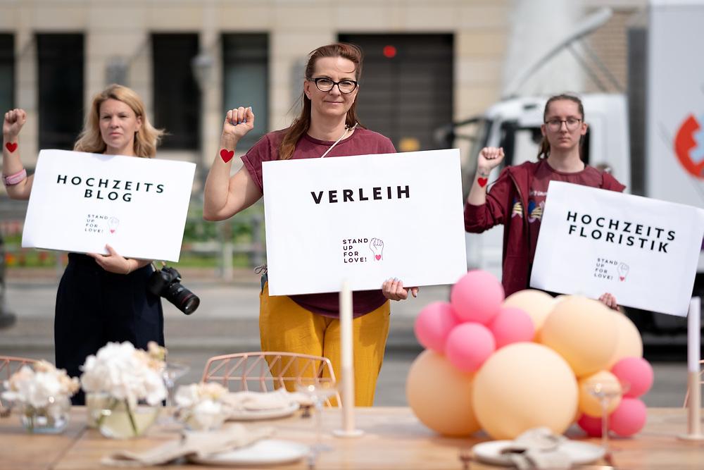 """An die 50 Beschäftigte in der Hochzeitsbranche protestieren unter dem Motto """"Stand up for love"""" vor dem Brandenburger Tor in Berlin. Sie kritisieren, dass viele Soloselbstständigen der Branche durch das Raster der Corona-Hilfspakete fallen und fordern einheitliche Regelungen, nach denen künftig Hochzeiten trotz der Corona-Pandemie stattfinden dürfen. <br /> <br /> <br /> [© Christian Mang - Veroeffentlichung nur gg. Honorar (zzgl. MwSt.), Urhebervermerk und Beleg. Nur für redaktionelle Nutzung - Publication only with licence fee payment, copyright notice and voucher copy. For editorial use only - No model release. No property release. Kontakt: mail@christianmang.com.]"""