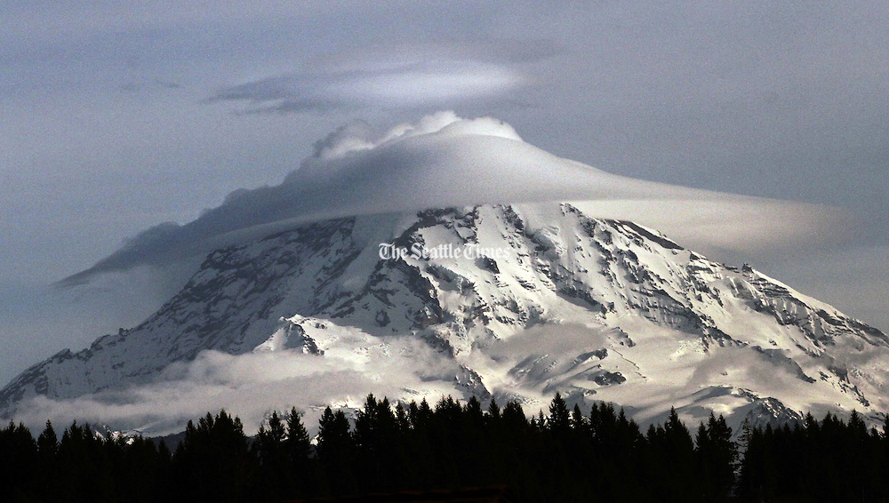"""Lenticular or """"cap clouds"""" form around Mount Rainier, often signaling a change in the weather. (Alan Berner / The Seattle Times)"""