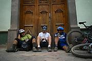 Antonio Acosta, Jose Antonio Borgoñon y Alonso Geminiano toman un descanso sentados frente a una puerta de madera en el centro de Zacatlan.