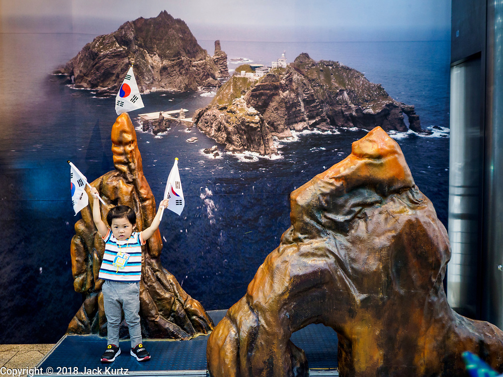 08 JUNE 2018 - SEOUL, SOUTH KOREA: A girl waves South Korean flags at a picture point in the War Memorial of Korea in Seoul, South Korea. The background of the picture point is Dokdo Island, a small islet about midway between Japan and South Korea. With the near constant threat of invasion from North Korea, many South Koreans take great pride in the ability of their armed forces. Some observers believe there is a possibility that a peace agreement between South and North Korea could be signed following the Trump/Kim summit in Singapore. The War Memorial and museum opened in 1994 on the former site of the army headquarters to exhibit and memorialize the military history of Korea. When it opened in 1994 it was the largest building of its kind in the world. The museum features displays about the Korean War and many static displays of military equipment.    PHOTO BY JACK KURTZ