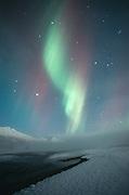 Alaska. Palmer. Aurora borealis or northern lights above Knik River and Chagach Mts.