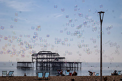 Licensed to London News Pictures. 06/09/2021. Brighton, UK. Sunbathers enjoy bubbles on Brighton Beach, East Sussex as weather forecaster predict a mini-heatwave for September this week with temperatures hitting over 29c tomorrow. Photo credit: Alex Lentati/LNP