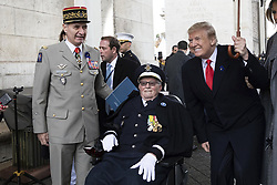 November 11, 2018 - Paris, France - U.S. President Donald Trump, right, poses with a veteran as General Jean-Pierre Bosser, French Army Chief of Staff looks on, left, following events marking the Centennial of Armistice Day at the Arc de Triomphe November 11, 2018 in Paris, France. Armistice Day marks the end of World War I. (Credit Image: © Shealah Craighead via ZUMA Wire)