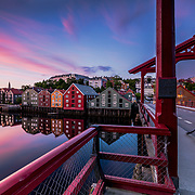 This is a midnight sunset around 11:45 p.m. The picture has been taken over gamlebybro (the bridge with the red color). This is an iconic element of the Trondheim. Trondheim with picturesque, tiny, wooden houses. This idyllic neighbourhood on the east side of the Nidelva river features old timber buildings, originally the homes of the working class. Now restored, Bakklandet is a charming mixture of houses, shops and cafés.<br /> Nidelva river cuts through the city, winding its way along the Nidarosdomen park and picturesque areas, with the historic, wooden wharf houses lining its sides towards the mouth at the Trondheim fjord, and the beautiful, wooden bridge amle Bybrocrossing the river. Please feel free to check my photos here or find me by: |Website| ,|Facebook page| , |Instagram| ,|Google+| ,|Twitter |.
