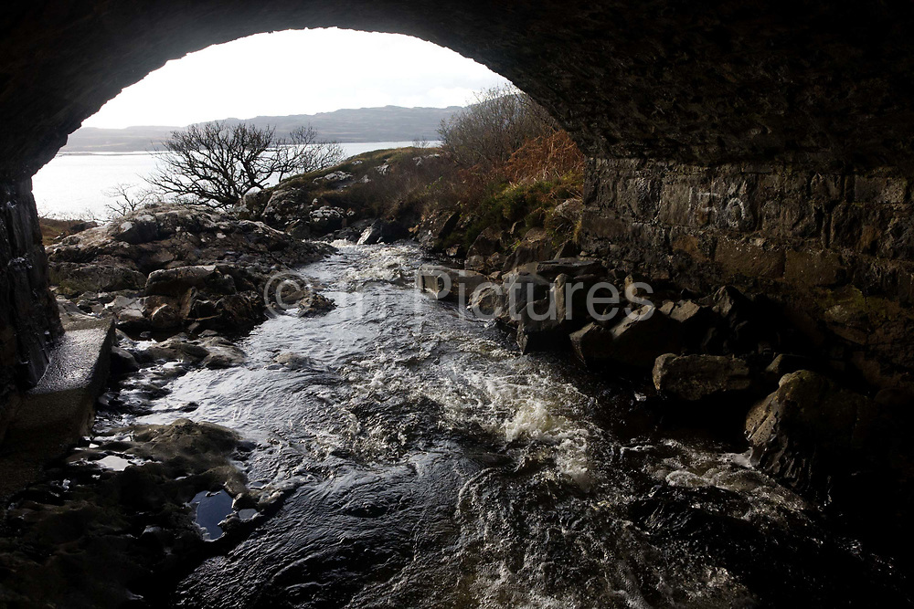 From beneath a stone bridge that crosses the Allt an Eas River at Eas Falls, near Kilbrennan, Isle of Mull, Scotland. The fast-flowing river curls downhill under the locally-sourced stonework to soon fall steeply into the distant Loch Tuath with the Island of Ulva, the headland beyond. Eas Fors Waterfall is one of the most spectacular waterfalls on the island, situated just off the B8073, a couple of miles North of Ulva Ferry. Eas is Gaelic for waterfall, Fors is Norse for waterfall and the final fall plunges 100 feet over the edge of the cliff to the sea below.