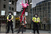 An animal rights activist stands between Metropolitan Police officers guarding the offices of Cargill during a National Animal Rights March by Animal Rebellion and other groups on 28th August 2021 in London, United Kingdom. Animal Rebellion, an offshoot of Extinction Rebellion, organised the march for the sixth day of Extinction Rebellions protests in London. Cargill is one of the worlds largest meat processors.