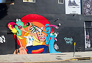 A colorful wall mural on Melrose Ave. in Los Angeles, California depicts goofy stylized creatures on a black background while above is an advertisement for Converse shoes.