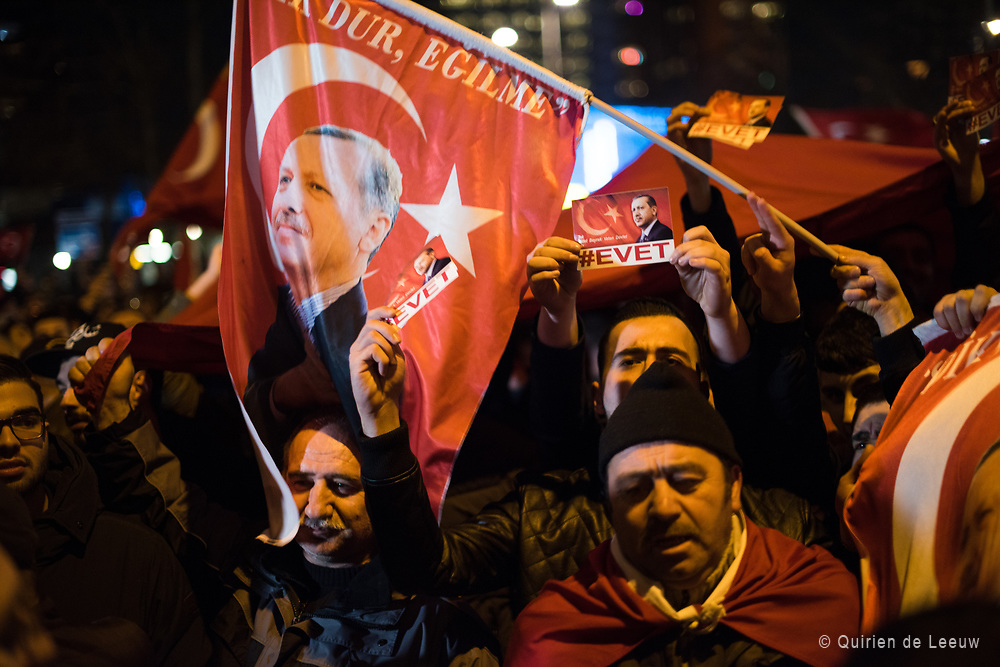 Demonstrators with banners of Turkish President Recep Tayyip Erdogan gather outsidethe Turkish consulate to welcome the Turkish Family Minister Fatma Betul Sayan Kaya, who decided to travel to Rotterdam by land after Turkish Foreign Minister Mevlut Cavusoglu's flight was barred from landing by the Dutch government, in Rotterdam, Netherlands