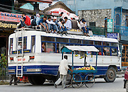 A man pushes a fruit stand on wheels, serving a crowded bus filled on the roof, in Pokhara, Nepal.