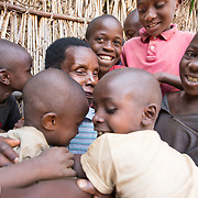 CAPTION: When Theresia came home after her operation, her grandchildren were overjoyed and couldn't stop telling her how good she looked. LOCATION: Rutare, Byumba-Gichumbi, Rwanda. INDIVIDUAL(S) PHOTOGRAPHED: Theresia Nzabamwita and unknown children.