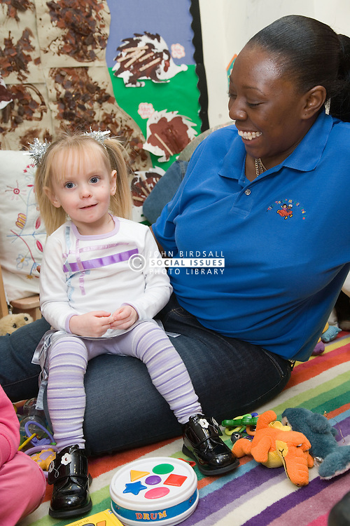 Nursery nurse; at work in mobile creche; with young girl; smiling,