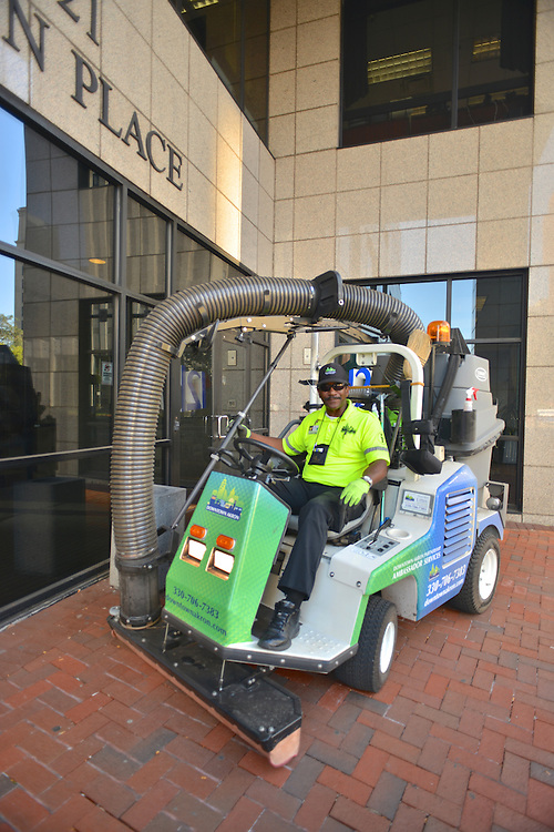 A Downtown Akron Partnership cleaning & safety ambassador cleaning the sidewalks.