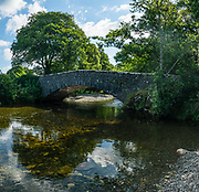 Old stone bridge over Esk River. Eskdale Trail, in Lake District National Park. England Coast to Coast hike with Wilderness Travel, day 2 of 14: from Eskdale in Cumbria county, we walked to Boot for lunch at a local pub and a visit to a working medieval corn mill, in the United Kingdom, Europe. We then climbed to Burnmoor Tarn, then descended to the hamlet of Wasdale Head. Via minibus we returned to Irton Hall for the second night. [This image, commissioned by Wilderness Travel, is not available to any other agency providing group travel in the UK, but may otherwise be licensable from Tom Dempsey – please inquire at PhotoSeek.com.] This image was stitched from multiple overlapping photos.
