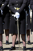 Female soldiers in military dress uniform with swords on parade at Sandhurst Royal Military Academy, Surrey, England