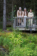 The K'Beq' Interpretive Site. The Sovereign Nation of The Kenaitze <br /> <br /> From left to right are Denali Bernard (age 15) and Julianne Wilson (age 20) and Emilee Wilson (age 13)<br /> <br /> All three live in Kenai and they have been involved in the Kenaitze Indian Tribe's Yaghanen Youth Programs since they were in 1st grade. They have participated in Yaghanen's Native Youth Olympics team, Jabila'ina Dance group, Del Dumi drum group and summer culture camps. Denali states that she enjoys being involved in the programs because they are fun and she gets to meet new friends.<br /> <br /> The dresses would have been traditionally made with caribou skins but the ones that the girls are wearing in the photo are replicas made from pig skin. The fur around the neck is sea otter. The dance group was given its' name by one of our Kenaitze Elders that has long passed. The name Jabila'ina means People of the Rainbow and is to signify that our group is made up from youth from all cultural backgrounds. Because of this we allow our youth to wear head dresses from their individual cultures if they wish. The Wilson girls are Dena'ina Athabaskan and Denali is of Inupiaq descent. The head dresses that they are wearing have traditionally within our dance group, signified that a girl has made the transition into womanhood. The cloths that they are holding are used only when dancing and only by the women.<br /> <br /> Photographer: Christina Sjögren<br /> <br /> Copyright 2019, All Rights Reserved