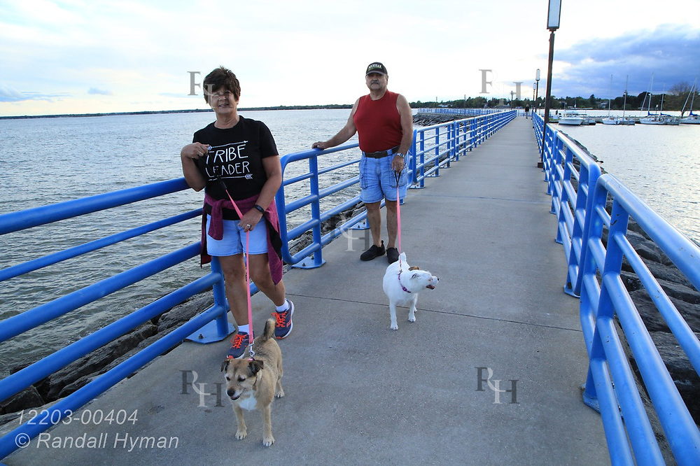 Man and woman walk their dogs along breakwater on a September afternoon in Alpena, Michigan.