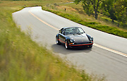 california-car-photographer-randy-wells-automotive-videographer-filmmaker-cinematographer-storyteller-writer-location-and-studio-specialist, Image of a man driving a black german 1973 Porsche 911 RS Carrera on a country road near Paso Robles, California, model and property released