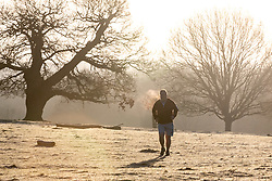 © Licensed to London News Pictures. 22/01/2021. London, UK. Walkers enjoy a frosty and misty sunrise with a low of -1 in Richmond Park South West London this morning. A chilly weekend ahead is forecast for the South East as the rain and wind from Storm Christoph subsides after it caused heavy snowfalls and flooding in the North of England this week. Photo credit: Alex Lentati/LNP