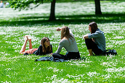 © Licensed to London News Pictures. 27/05/2021. LONDON, UK.  People enjoying the sunshine and warmer temperatures in St James's Park amongst the daisies after an unusually wet May so far.  The forecast for the Bank Holiday weekend is fine weather.  Photo credit: Stephen Chung/LNP