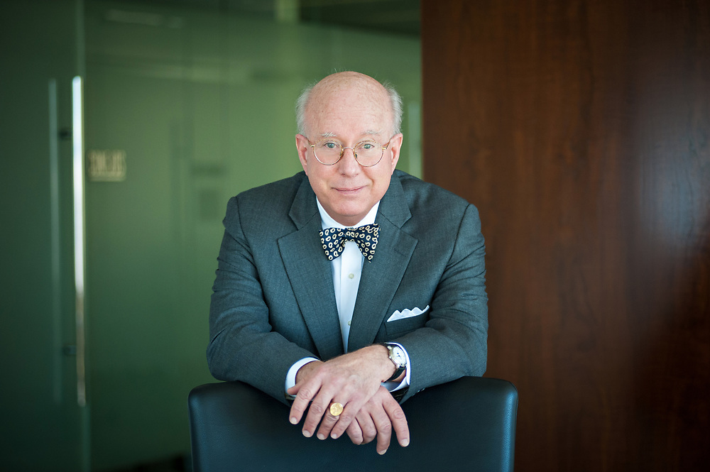 Portrait of a lawyer leaning on a chair in Denver, Colorado wearing a bow tie