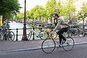 In Amsterdam rijdt een man al bellend door de binnenstad op een racefiets.<br /> <br /> In Amsterdam, a man drives while phoning through the city on a road bike.