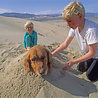 Youngsters bury their patient dog in a sand dune in Eureka Valley, part of California's Death Valley National Park.
