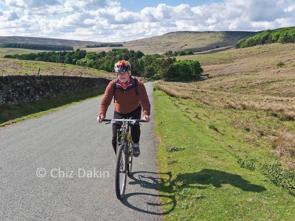 Andy cycling up the hill from Stanage Plantation under Stanage Edge