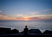 Man kijkt naar zonsondergang op het havenhoofd, Scheveningen, Den Haag. - Man is watching sunset at the pier, Scheveningen, The Hague, Netherlands