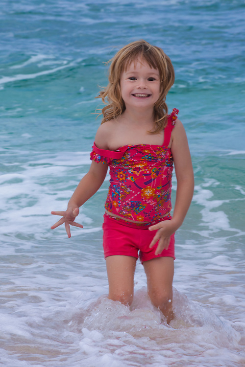 A little girl playing in the shorebreak on the beach in Hawaii