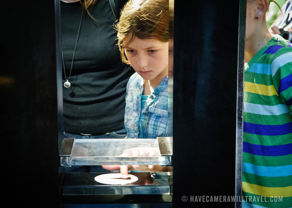 A young girl visiting the National Air and Space Museum in Washington DC touches a piece of moon rock near the main entrance.