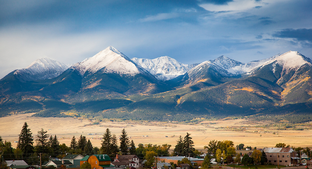 Horn Peka and the Sangre de Cristos, topped with morning clouds and dressed in yellow aspens, rise behind the Town of Westcliffe early on a fall morning.