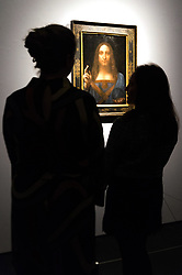 © Licensed to London News Pictures. 24/10/2017. London, UK. Christie's staff members view a painting titled Salvator Mundi (1490) by artist Leonardo da Vinci with an estimate in excess of 00 million. The painting of Christ as Salvator Mundi was recently attributed to Leonardo da Vinci, who is known to have painted the subject. It was lost and later rediscovered, and restored and exhibited in 2011. Photo credit: Ray Tang/LNP