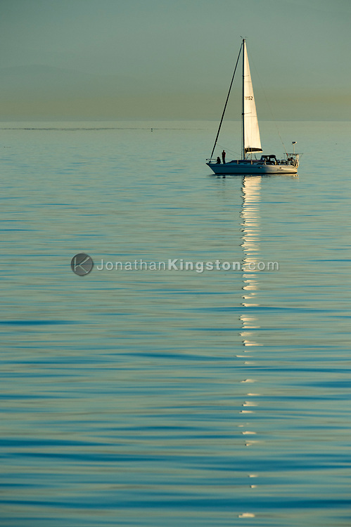 A sailboat and it's reflection in the calm waters near Friday Harbor, Washington, USA. A layer of smog is visible in the background.