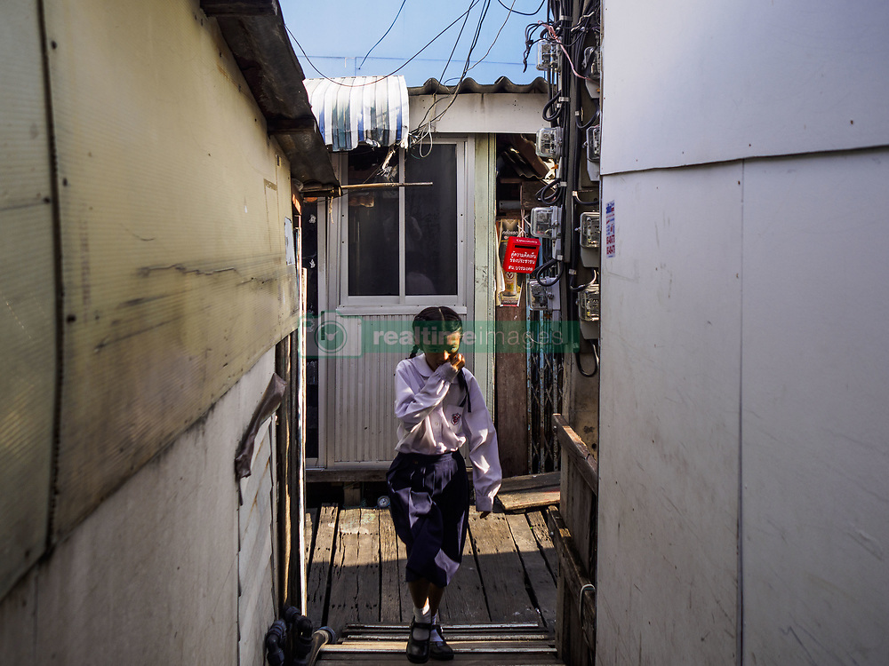 June 20, 2017 - Bangkok, Bangkok, Thailand - A schoolgirl walks home in a community along the Chao Phraya River south of Krung Thon Bridge. This is one of the first parts of the riverbank that is scheduled to be redeveloped. The communities along the river don't know what's going to happen when the redevelopment starts. The Chao Phraya promenade is development project of parks, walkways and recreational areas on the Chao Phraya River between Pin Klao and Phra Nang Klao Bridges. The 14 kilometer long promenade will cost approximately 14 billion Baht (407 million US Dollars). The project involves the forced eviction of more than 200 communities of people who live along the river, a dozen riverfront  temples, several schools, and privately-owned piers on both sides of the Chao Phraya River. Construction is scheduled on the project is scheduled to start in early 2016. There has been very little public input on the planned redevelopment. The Thai government is also cracking down on homes built over the river, such homes are said to be in violation of the ''Navigation in Thai Waters Act.'' Owners face fines and the possibility that their homes will be torn down. (Credit Image: © Jack Kurtz via ZUMA Wire)