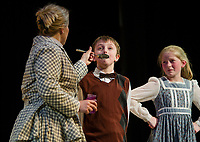 """Kelli Powers as Mary Poppins gives Jesse Powers as Michael """"a teaspoon of sugar to help the medicine go down"""" with Isabella Cottrell as Jane during dress rehearsal for The Streetcar producation of """"Mary Poppins"""" at InterLakes High School auditorium.  (Karen Bobotas/for the Laconia Daily Sun)"""
