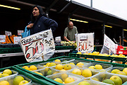 As a woman holding a shopping bag passes in the background, rows of fresh lemons and limes are displayed at an outdoor fruit and vegetable market stall on 4th September, 2021 in Leeds, United Kingdom. A combination of Brexit and Covid-19 is reportedly exacerbating an already severe staff shortage in the British food industry, with a lack of fruit and vegetable pickers that could see a hike in food prices across the country.