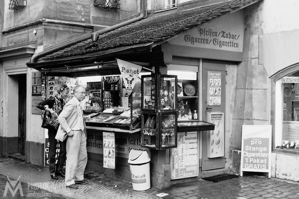Two people buying something at the kiosk. City life. - Berne, Switzerland - Zytglogge.<br /> <br /> (Analog black and white image. Scan from manually developed negative.)