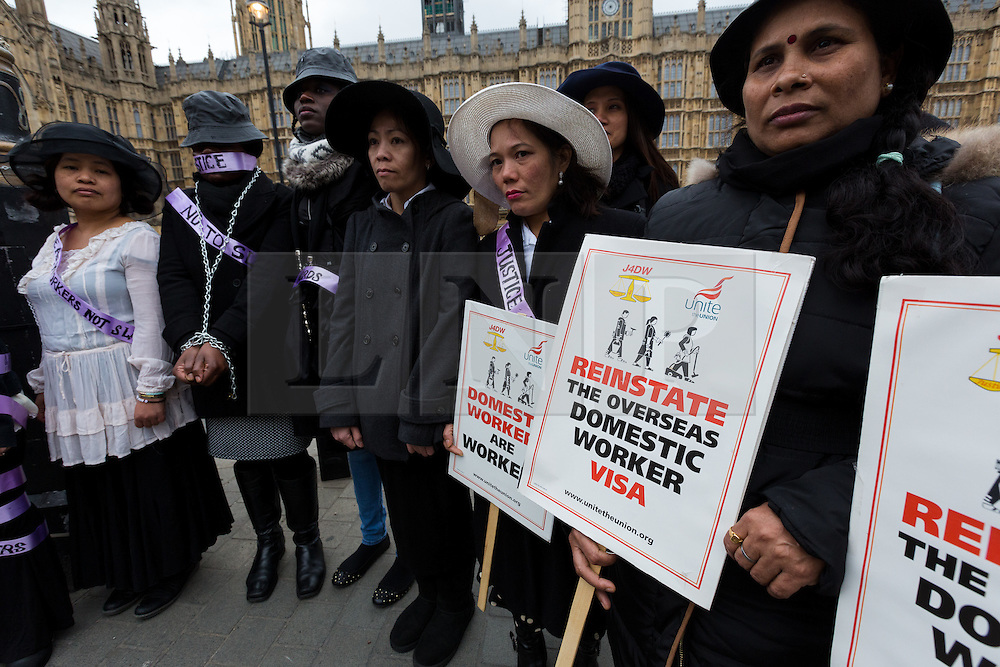 © Licensed to London News Pictures. 08/03/2015. London, UK. Domestic workers from Justice 4 Domestic Workers (J4DW) re-enact being suffragettes outside the Houses of Parliament to highlight the quest for domestic worker equality on International Womens Day. The demonstration follows a recent House of Lords amendment to the Modern Slavery Bill which will, if made law, will allow migrant domestic workers to change employers once in the UK. The amendment will be heard by Members of Parliament (MP's) in the House of Commons within the next week for the third and final reading. Photo credit : Vickie Flores/LNP