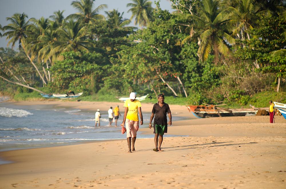 Fishermen walk along Matara beach in Sri Lanka