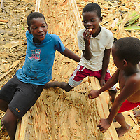 Boys lingering around a canoe still being carved from a tree at a small beach in São Tome's north shore.
