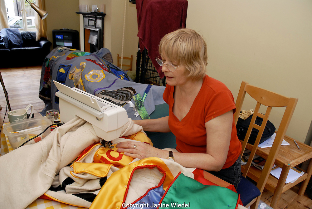 Textile artist sewing banners at home